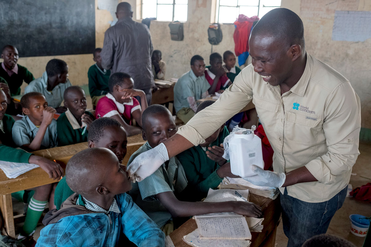 World Concern staff Harrison Macharia distributes deworming medication to elementary students near Narok, Kenya.